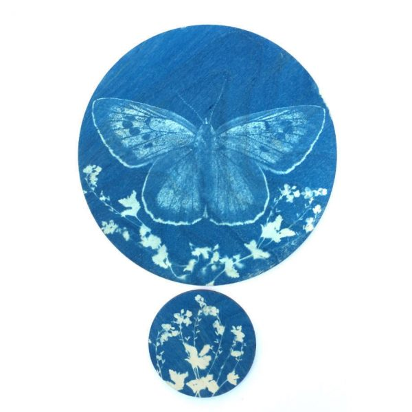 Blue butterfly on a wooden disc above a smaller wooden disc with floral design silhouette